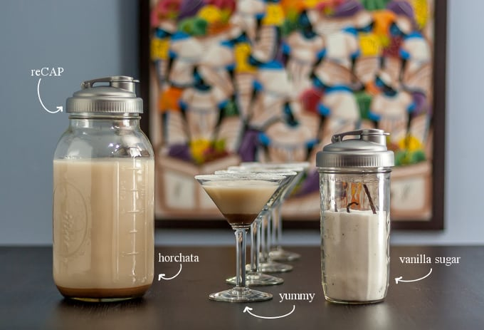 Horchata with reCAP mason jar a line of martini glasses and a jar of vanilla sugar