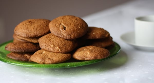 a green plate stacked with hermit cookies