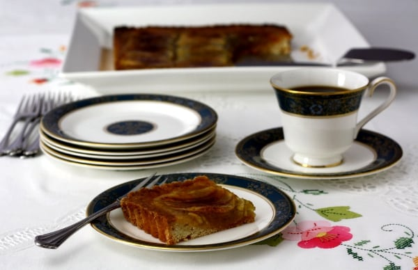 a slice of french apple art on a plate with coffee on the right and an entire tart in the back