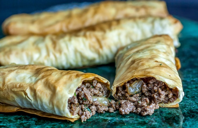 meat filled pastries cut in half with meat spilling out