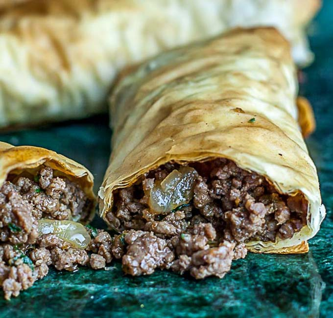 a burek cut in half with meat falling out