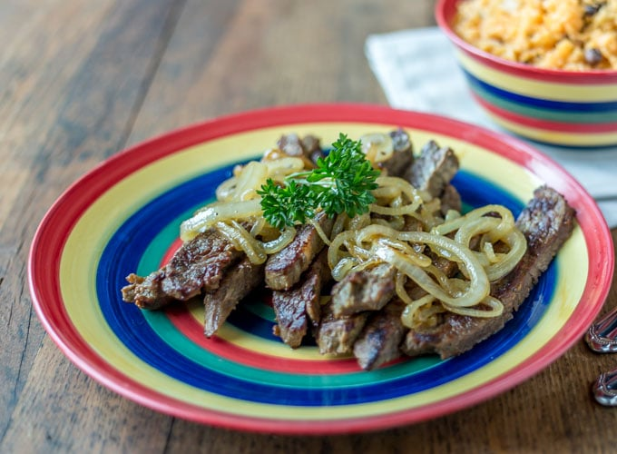 a close up on a plate of strips of steak with caramelized onions and parsley