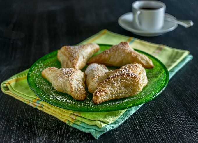 Pastelitos de guava turnovers on a green plate with a cup of coffee in back
