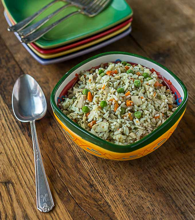 a closeup bowl of rice, chicken, peas, and carrots on a wooden table with a spoon