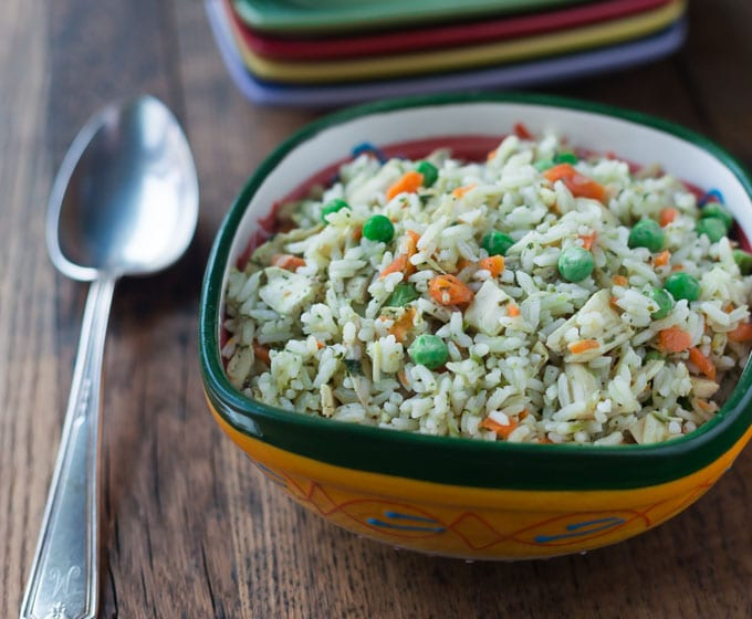 a closeup of a bowl of rice, peas, carrots, and a spoon on the left