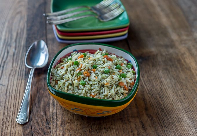 A bowl of rice with peas, carrots, and chicken on a wooden table
