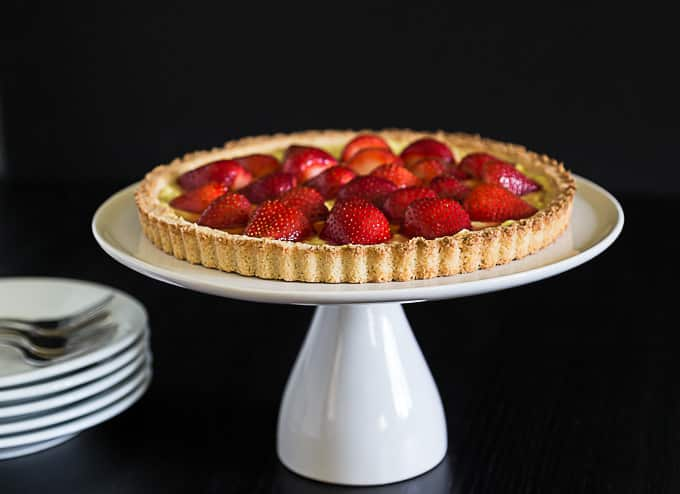 a sideview of a strawberry tart on a white cake riser