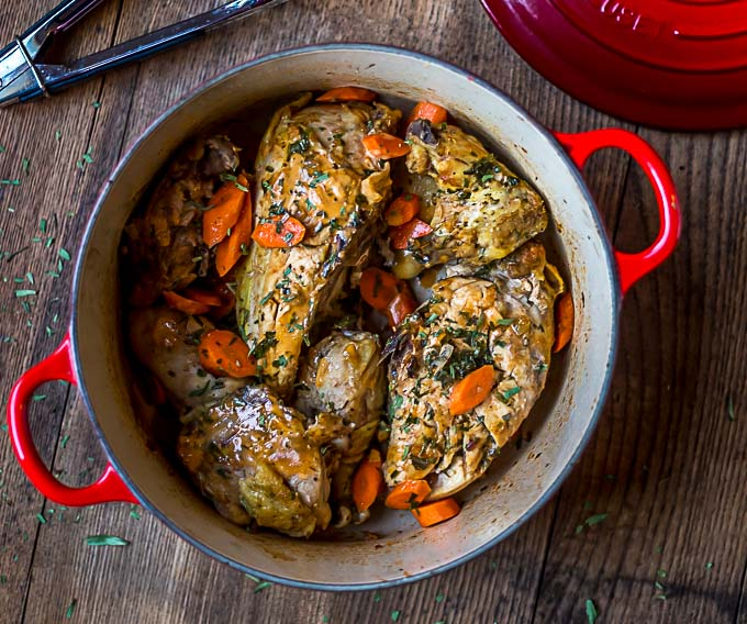 a closeup of a red dutch oven with tongs and tarragon chicken