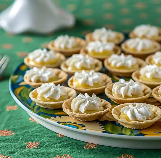 a closeup of mini lemon tartlets with whip cream
