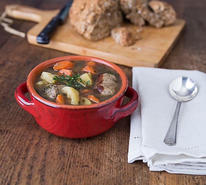 a red dish filled with irish stew a spoon on the left and bread in the back