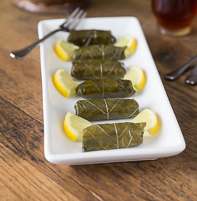 stuffed grape leaves on a plate with lemon wedges and a fork