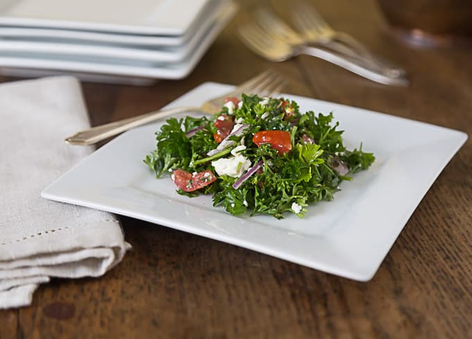 a plate of mediterranean parsley salad and a fork with a napkin on the left