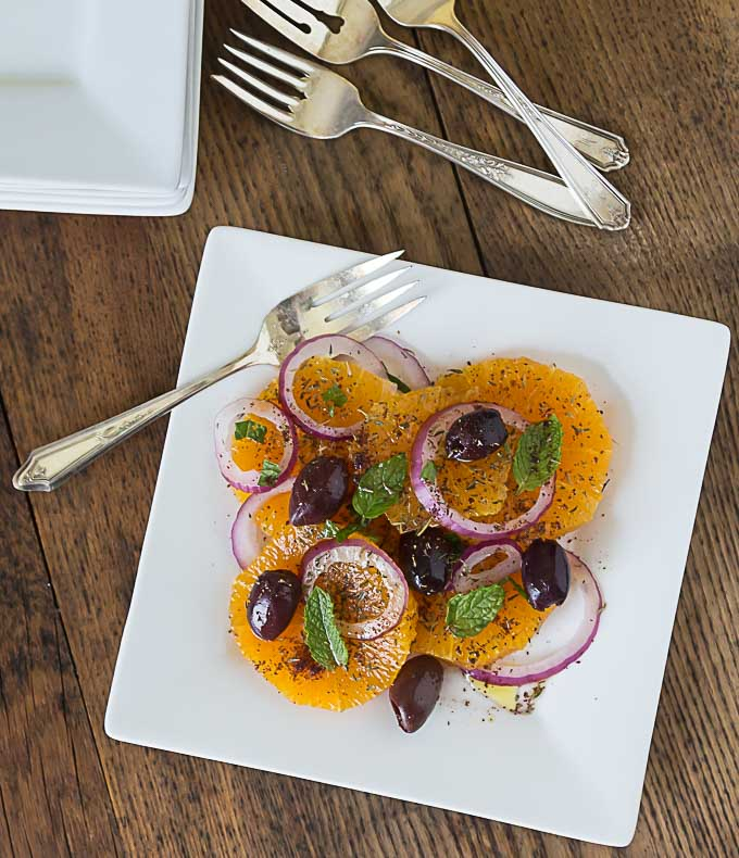 a top dow view of a white plate with turkish orange and onion salad with forks on the top