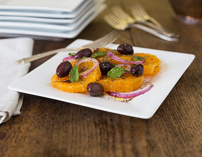 a white plate with turkish orange and onion salad with olives and mint leaves