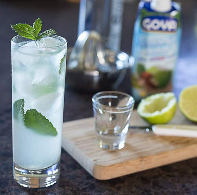 coconut mojito in a glass with a cutting board, limes, a knife, and a shot glass on the right