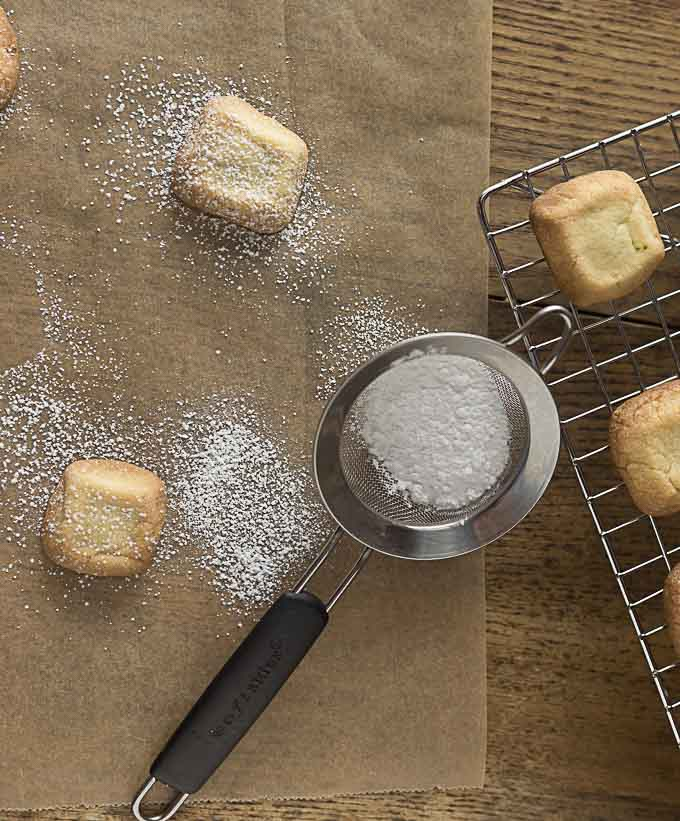 shortbread cookies getting dusted with powdered sugar