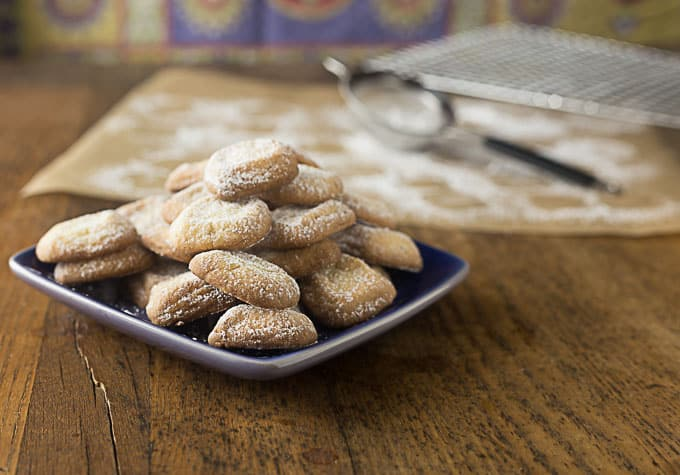 a plate of powder sugared shortbread cookies with parchment paper in the back