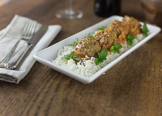 a white plate with lamb meatballs over rice decorated with mint leaves with a fork and knife on the right