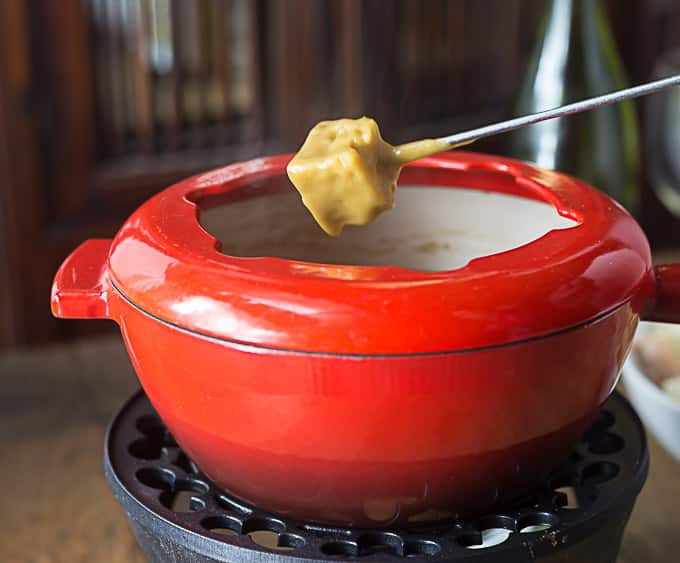 a red fondue pot with a fondue fork dipping bread in the pot