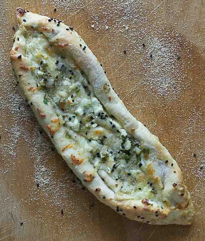 a turkish pastry, pide, on a wooden cutting board