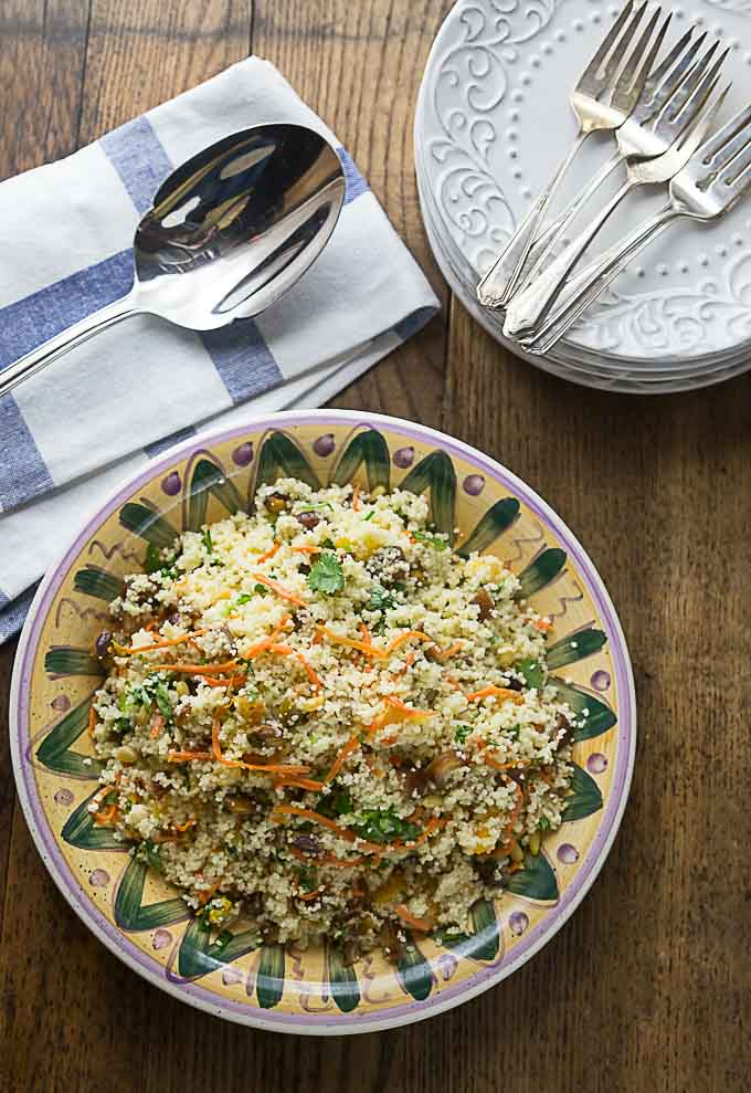 a plate of Turkish couscous salad with a spoon and a stack of plates around the dish
