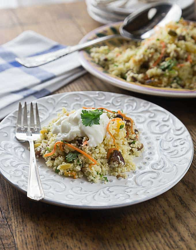 a white plate with cous cous topped with yogurt and cilantro with a fork and serving dish in the background