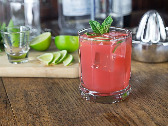 a pink guava cocktail with limes and a juicer in the back