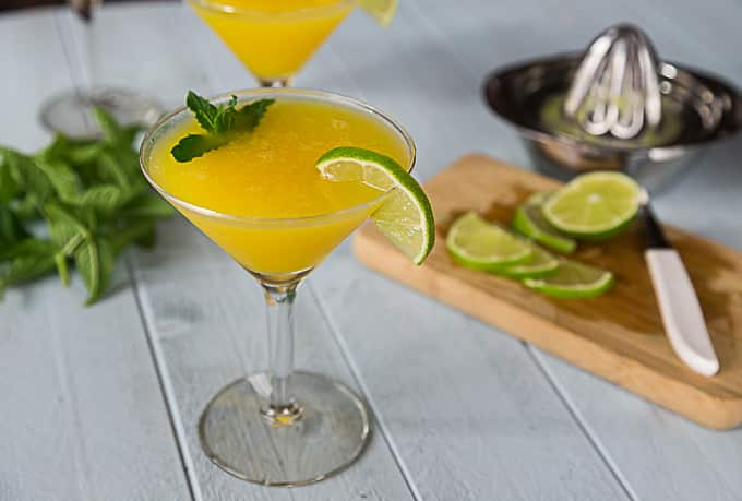 a martini glass with a yellow mango cocktail with mint and a lime wedge with cut up lime and a juicer in the back