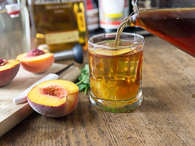 cut up peaches and a glass with peach cocktail getting poured
