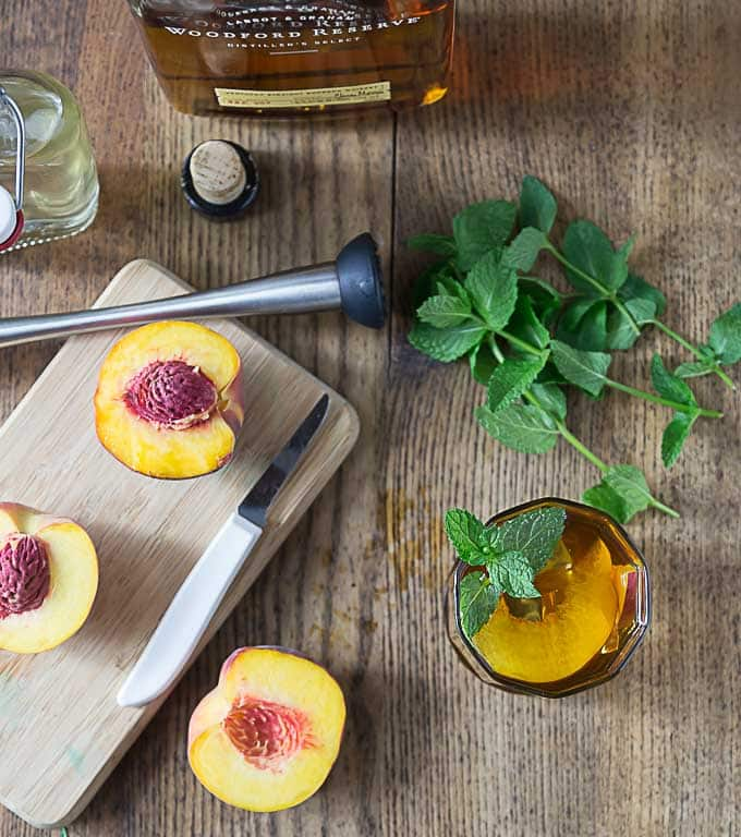 a wooden cutting board with peach halves, a bottle of bourbon, mint, and a cocktail