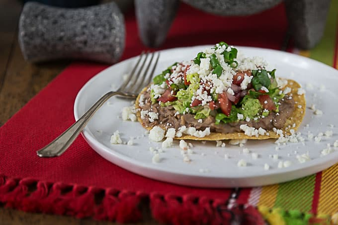a sideview of a tostada on a white plate with a fork