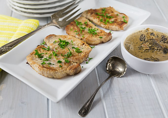 four pork chops on a plate with parsley and a bowl of mushroom sauce on the right