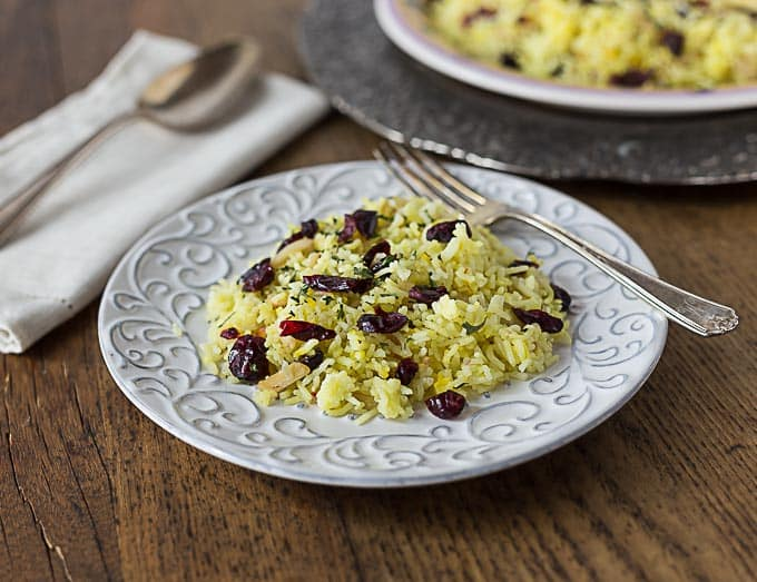 saffron rice with craisins on a white plate with a fork and a spoon and napkin on the left