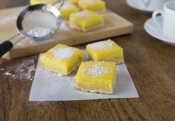 three mango lime bars on wax paper with powdered sugar and more bars in the back on a wooden cutting board
