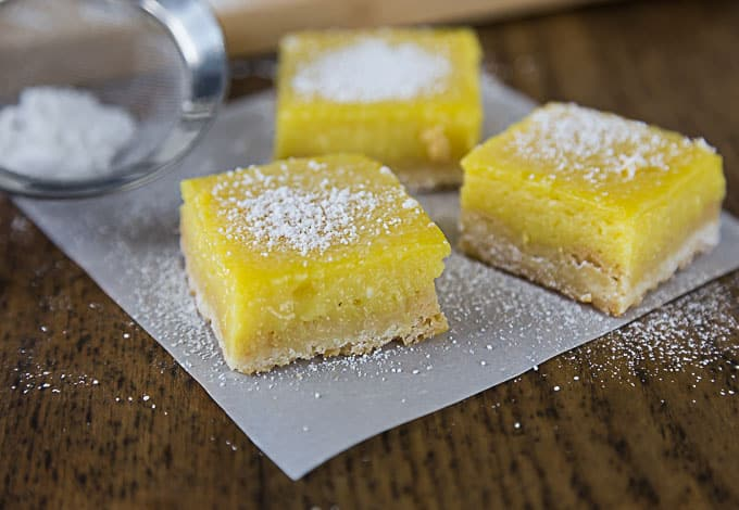 three mango lime bars on wax paper topped with powdered sugar