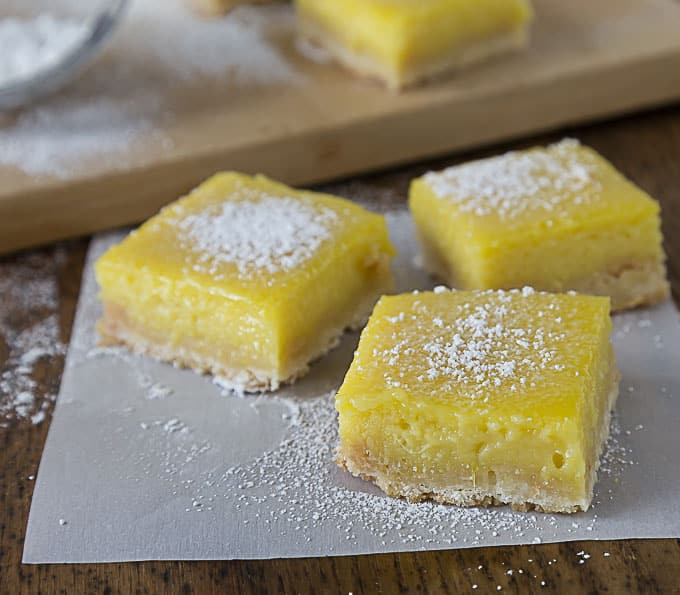 three mango lime bars on parchment paper with powdered sugar with a cutting board in the back