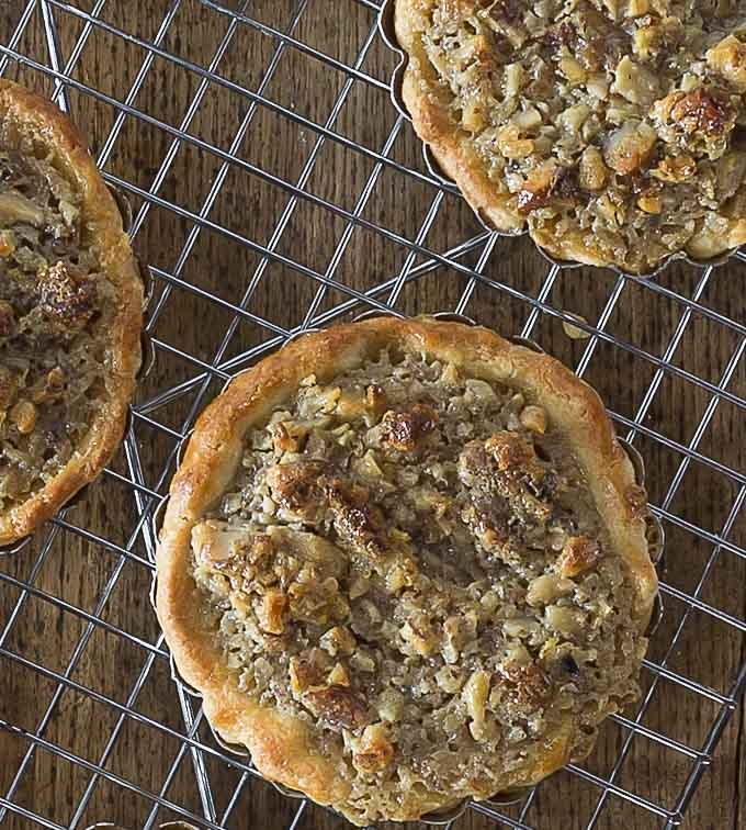 You will love these Tartelettes au Noix! French walnut tartlets are crunchy and creamy caramelized filling with a hint of orange and similar to pecan pie.   ethnicspoon.com