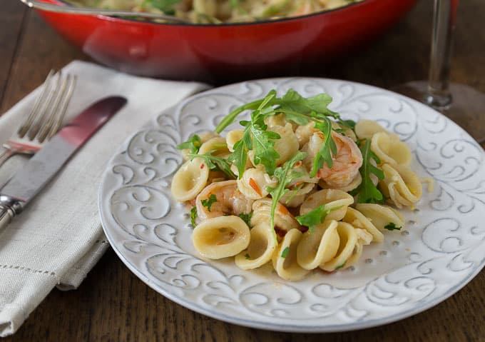 a white plate with orrechetti pasta, shrimp, and arugula with a knife and fork on a napkin on the left