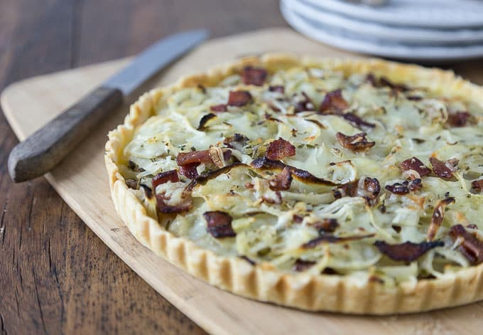 a potato bacon gruyere tart on a wooden cutting board with a knife