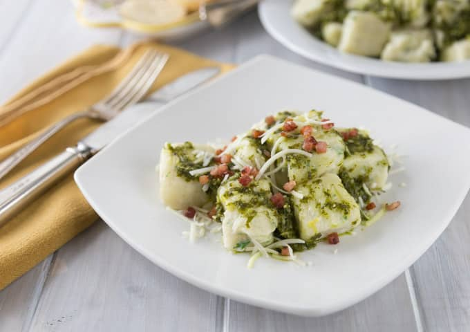 My new favorite Italian food recipe! Try this creamy and rich ricotta gnocchi with a nice lemony arugula pesto and tasty salty bits of pancetta! Everything is better with bacon right? The texture of the gnocchi has a nice firm outside and soft cheesy middle. This is a must try recipe. Buon appetito! | ethnicspoon.com