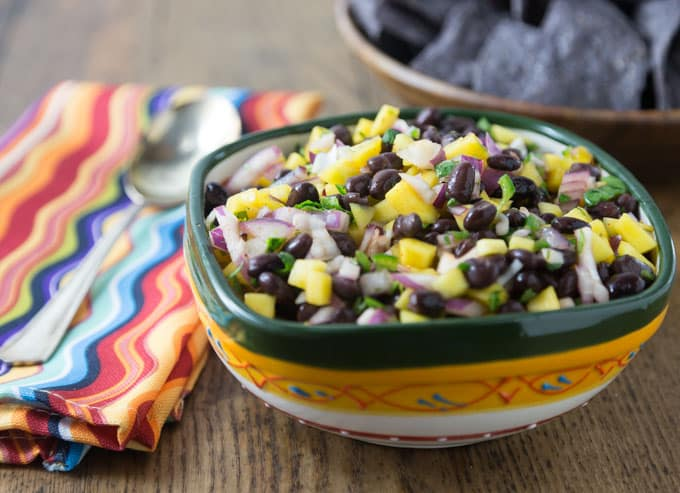 a bowl of mango black bean salsa with a striped napkin and a spoon on the left