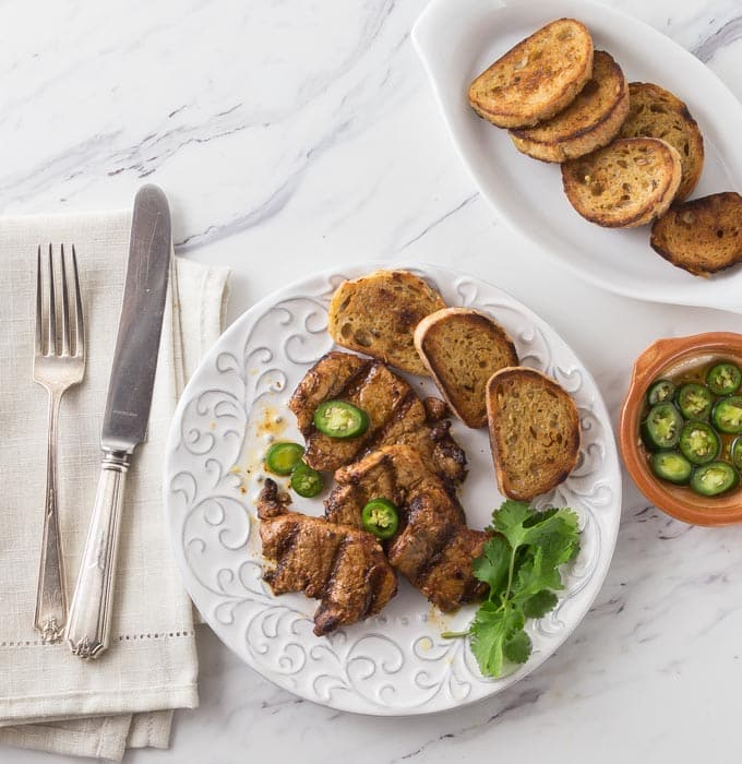 How about a classic Spanish tapas dish! Spicy marinated pork tenderloin medallions in paprika marinade and flash grilled al la plancha or al carbon. | ethnicspoon.com