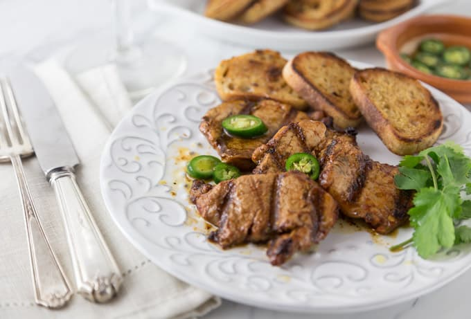 Spice up your summer grilling with this classic Spanish tapas dish! Spicy marinated pork tenderloin medallions in paprika marinade and flash grilled al la plancha or al carbon. | ethnicspoon.com