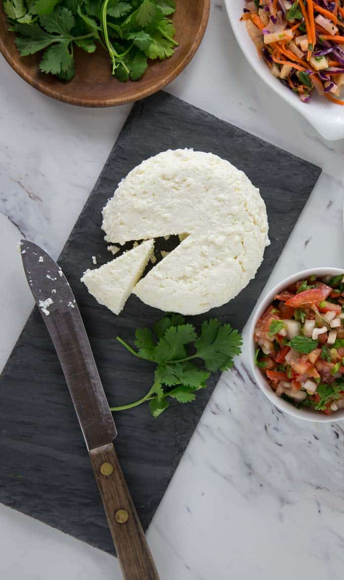 a black slate with farmers cheese sliced and some cilantro with bowls of slaw and more cilantro
