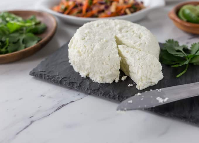 a round of homemade cheese on a slate with a plate of cilantro on the left