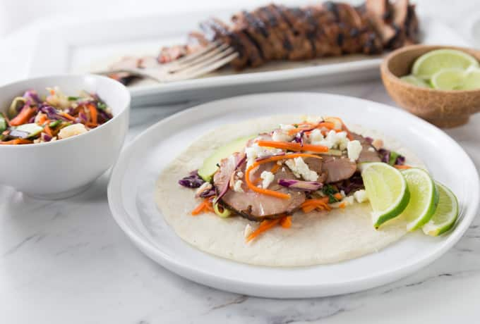 Tex Mex tacos on the grill make a quick and easy weeknight meal. You are going to love these tender thin slices of pork tenderloin for your next taco night! Get your grill on with some Texas smokehouse dry rub seasoned pork tenderloin. Add a little queso fresco, crunchy red cabbage slaw and sour cream to top it off. | ethnicspoon.com