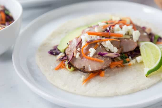 Here are some really tasty tacos! You are going to love these tender thin slices of pork tenderloin for your next taco night! Get your grill on with some Texas smokehouse dry rub seasoned pork tenderloin. Add a little queso fresco, crunchy red cabbage slaw and sour cream to top it off. | ethnicspoon.com
