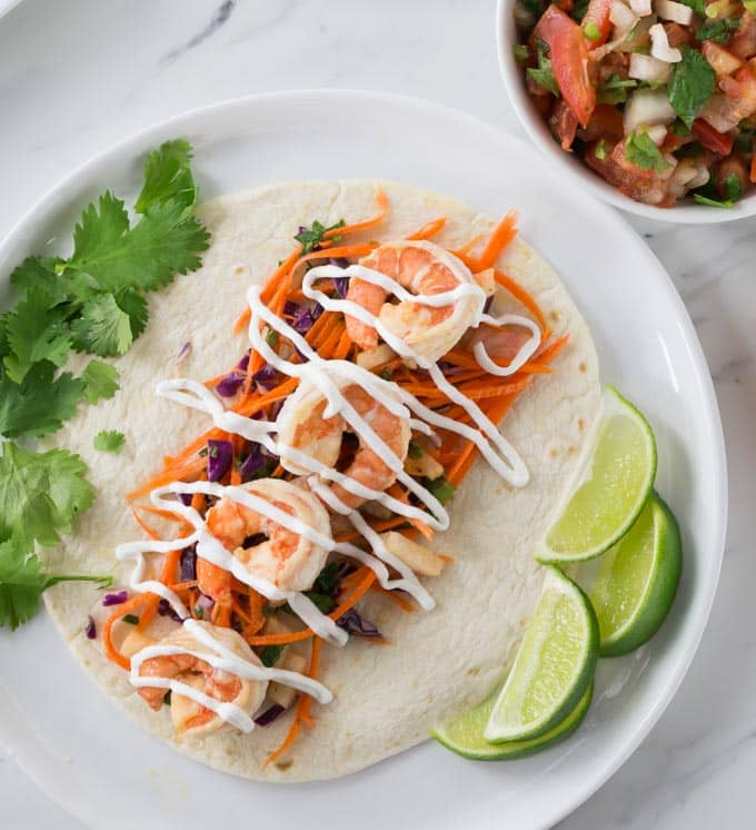 You are going to love these spicy shrimp tacos with jicama slaw. This recipe comes together very quick so it's a must try for a fast weeknight meal too! The jicama (hee cah ma) slaw has carrot sticks, and red cabbage. It rocks! It's colorful to say the least. It's a perfect complement to the soft shrimp. | ethnicspoon.com
