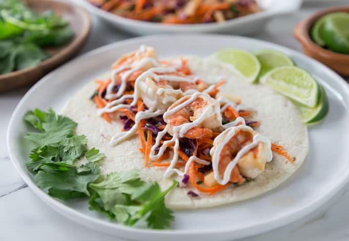 You are going to love these spicy shrimp tacos with jicama slaw! Layer some carrot sticks, red cabbage and chopped jicama on a warm tortilla with some spicy shrimp and sour cream. This recipe comes together very quick so it's a must try for a fast weeknight meal too! The jicama (hee cah ma) slaw has a nice crunch and it's tasty and colorful. It's a perfect complement to the soft shrimp. | ethnicspoon.com