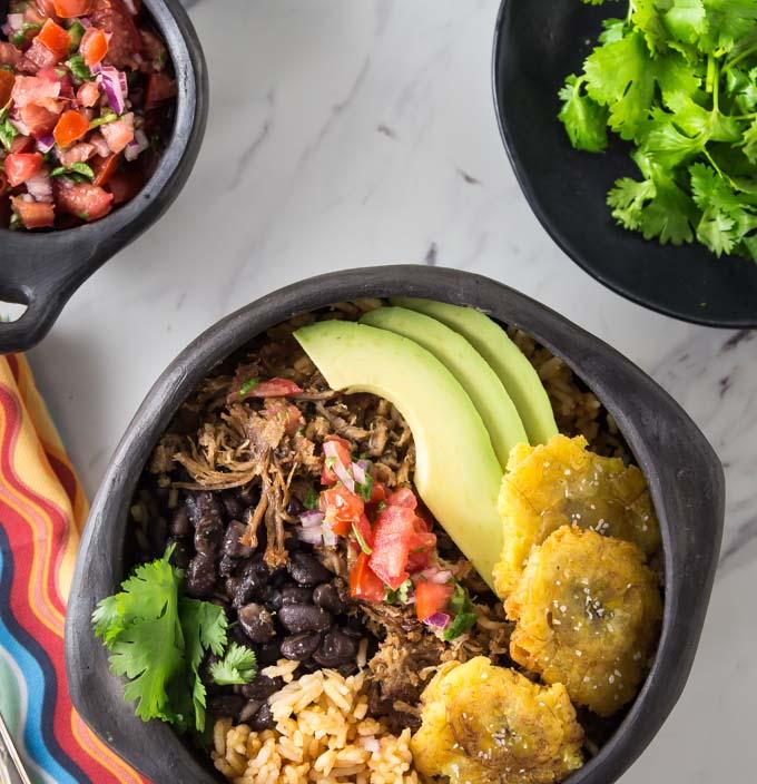 a pork carnitas bowl with sliced avocado, salsa, plantains, beans and rice
